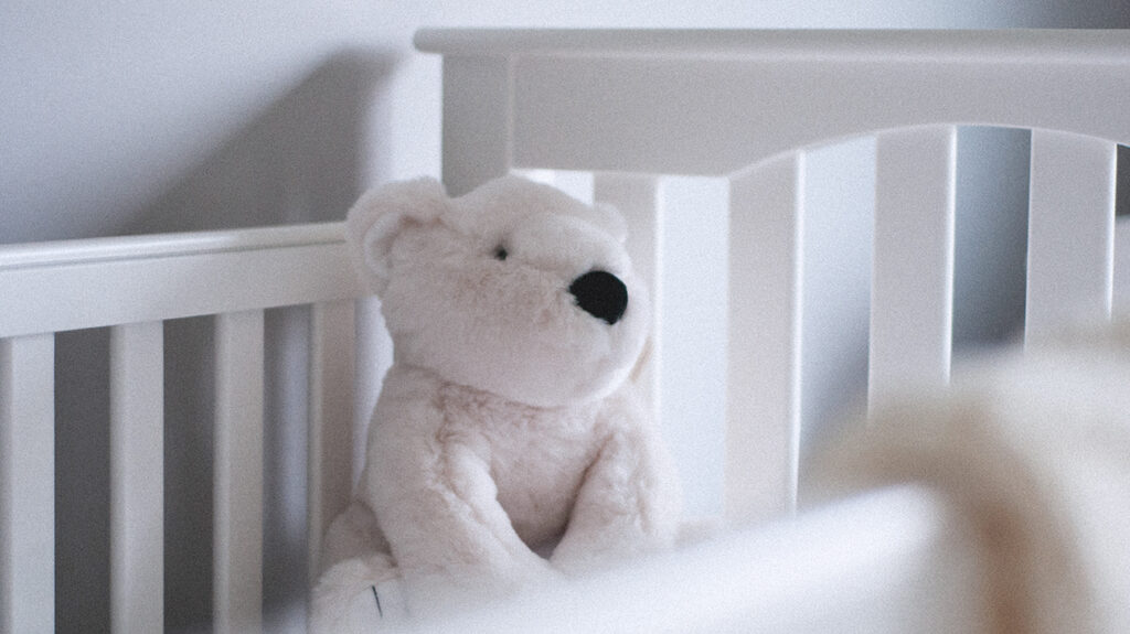 Empty white cot with teddy bear representing late miscarriage
