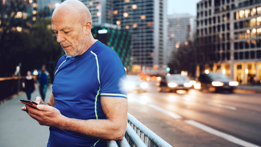 A man in running gear checking his phone