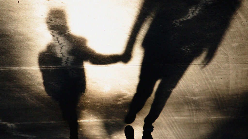 Distorted shadows of an adult holding a child's hand, to accompany an article on covert incest.