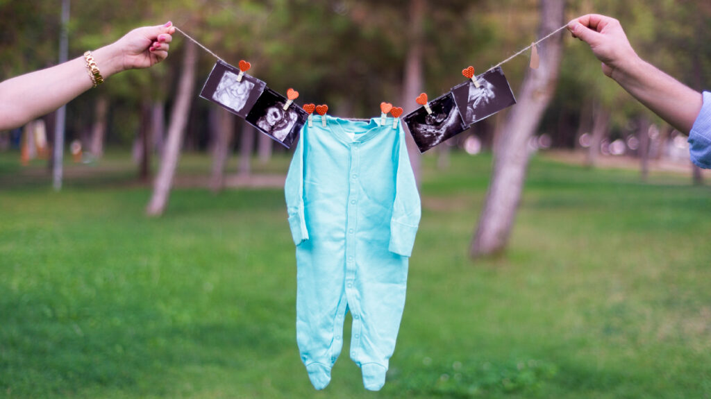Two hands outdoors holding up a clothesline with ultrasound photos and baby gro attached to announce pregnancy
