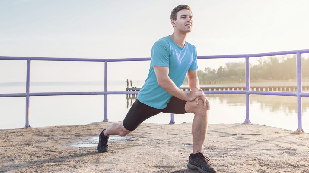 Person doing lunges outdoors as part of daily stretching routine