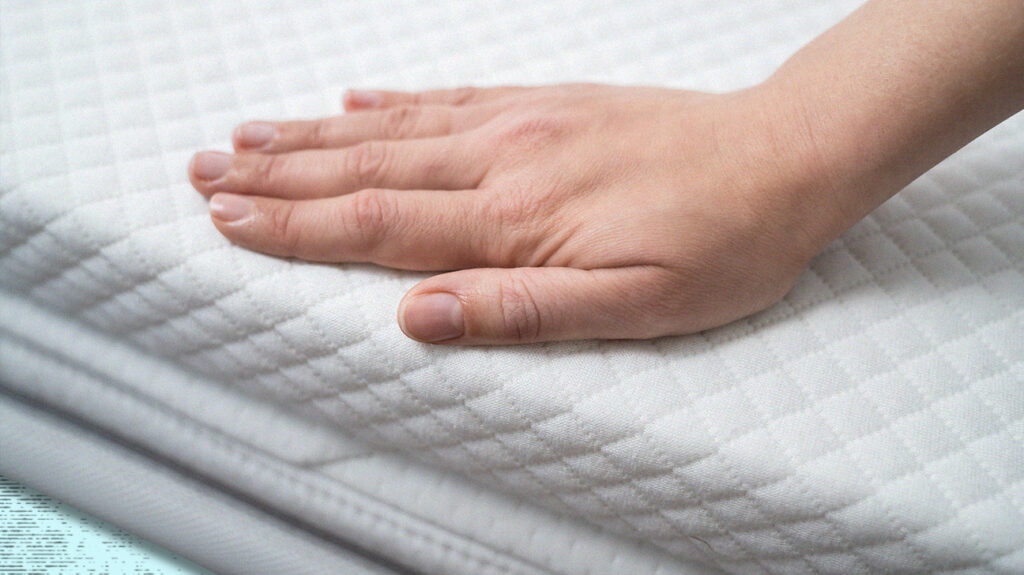 Person with their hand on a firm mattress topper