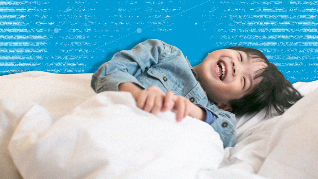 Happy laughing child in bed on a mattress for kids