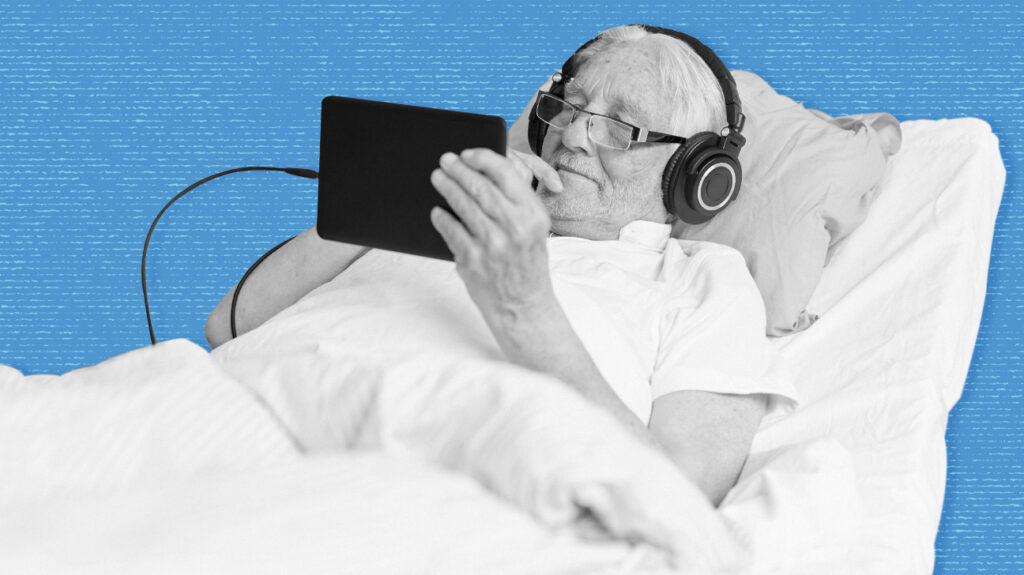 Black and white photo of an older adult in a hospital bed on a mattress, wearing headphones and watching tablet, isolated on blue background