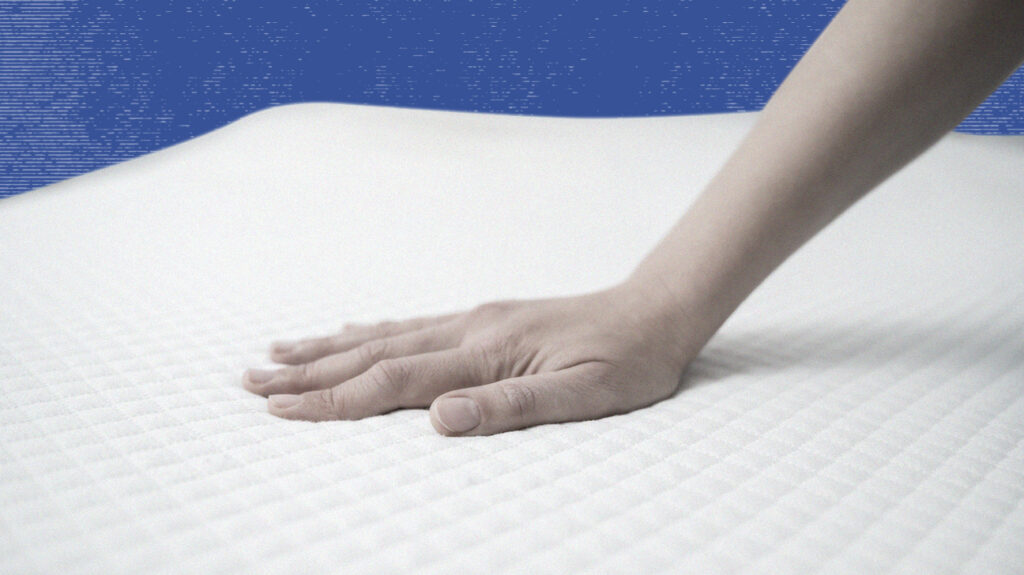 Person pressing hand onto mattress testing for for motion isolation