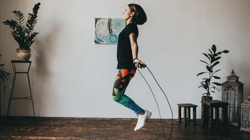 a woman performs cardio exercises at home by skipping with a jump rope