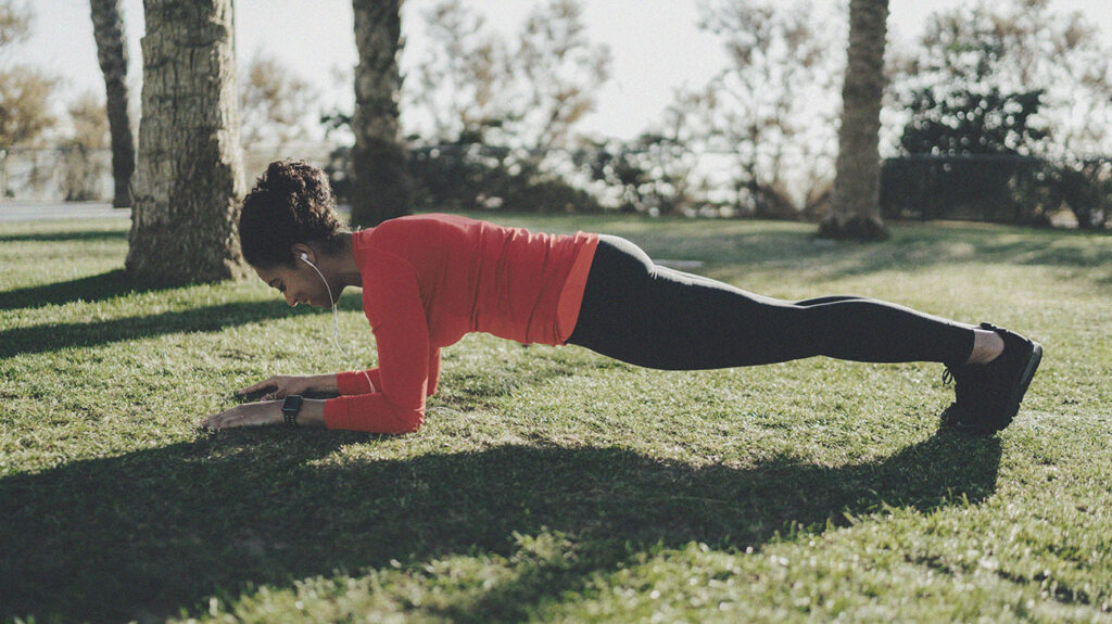 a woman performs one of the core exercises known as the plank in a public park