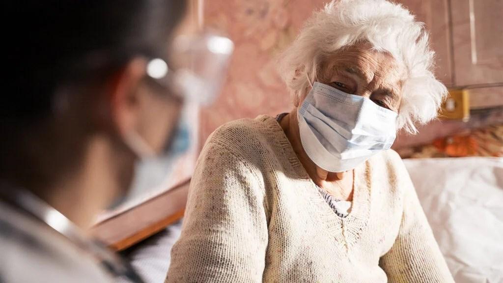 戴口罩接受专业人员护理的老年妇女