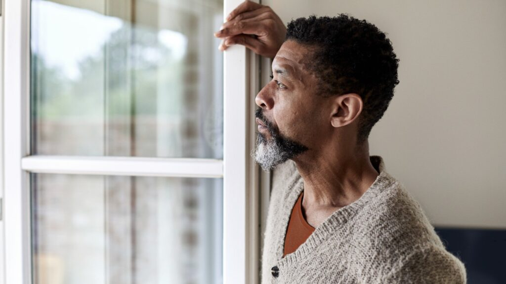Senior man with ed looking out of window wondering about a cure