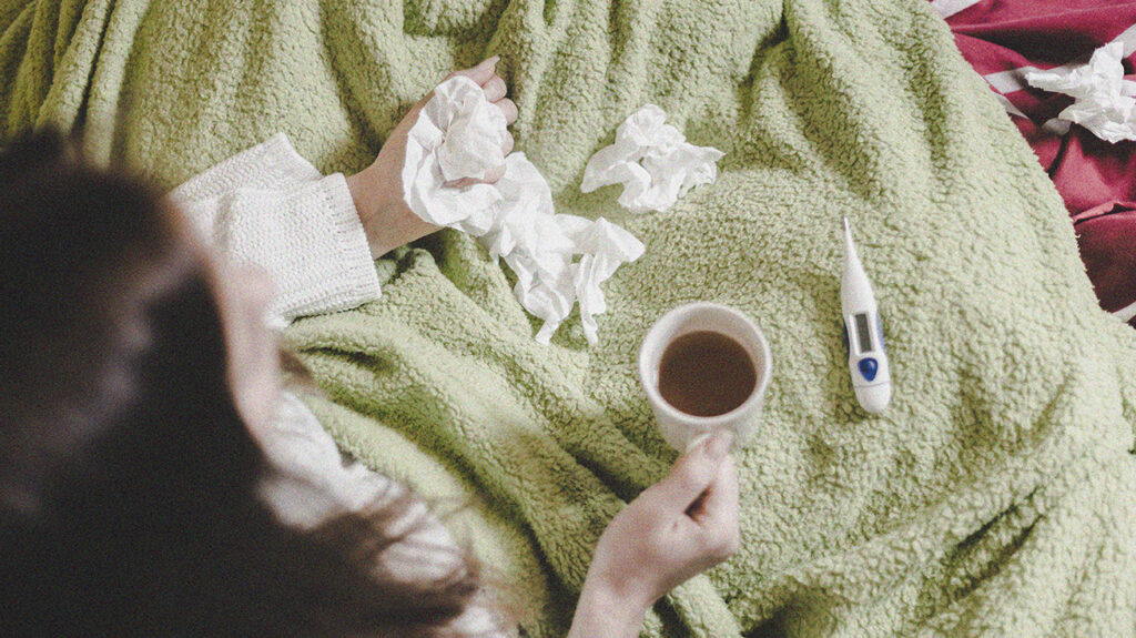 A brunette woman sitting in bed under a blanket, with tissues and a thermometer, thinking about whether she has a common cold or COVID-19.