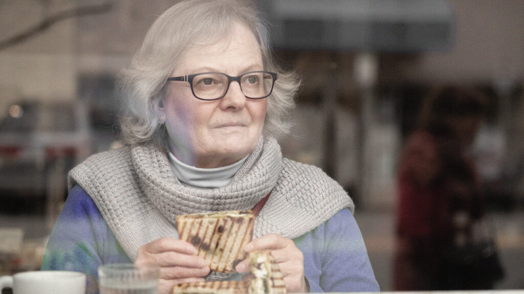 close up of older woman looking through the window of a cafe eating a sandwich