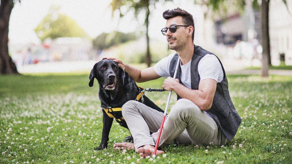 A man with vision loss sitting on the grass with his guide dog.