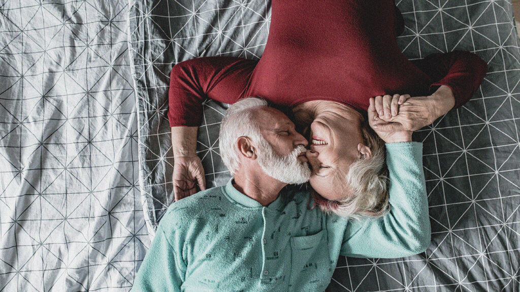 Older adult couple laying fully clothed on a bed playfully smiling with the older adult male kissing the older adult females nose while their hands are interlocked after asking does Medicare cover penile implants