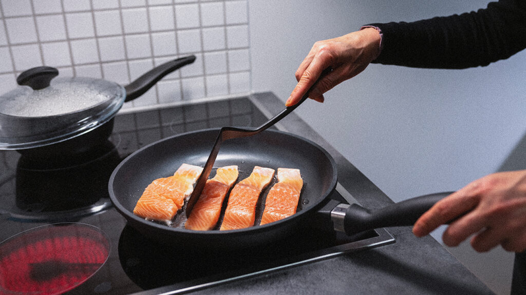 Someone cooking fish in a frying pan