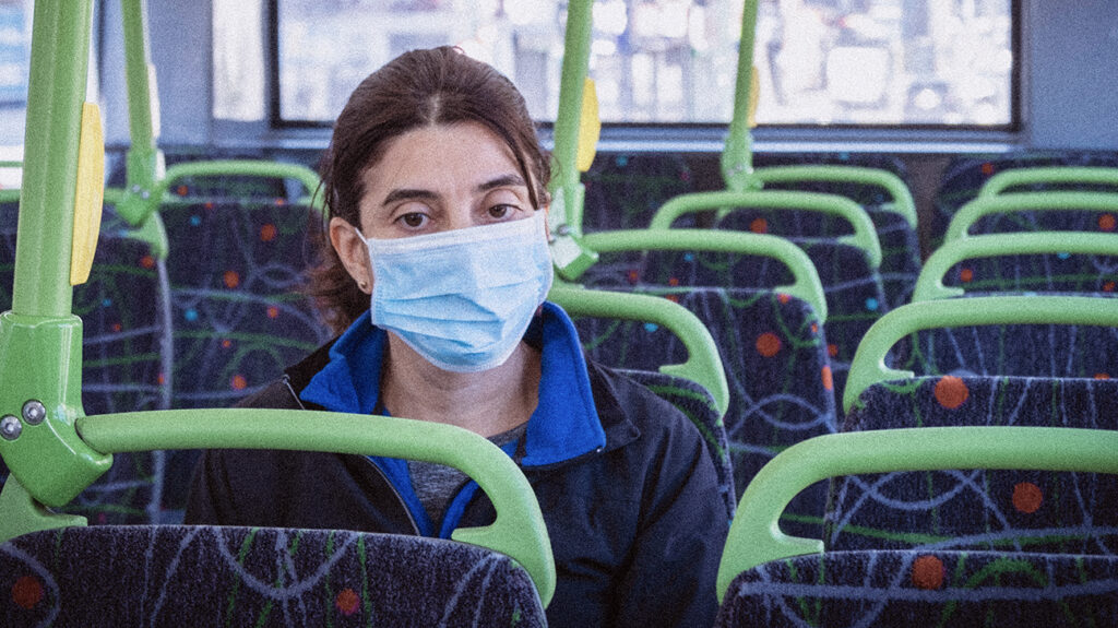 A female commuter wearing a face mask sits on a bus to accompany an article about COVID-19 live updates.