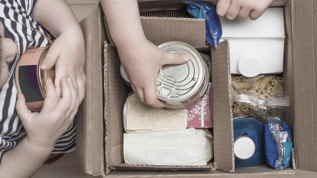 把食品罐头放进纸箱的手的特写