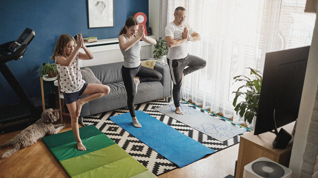 a group of people experience the benefits of exercise by performing yoga in a living room