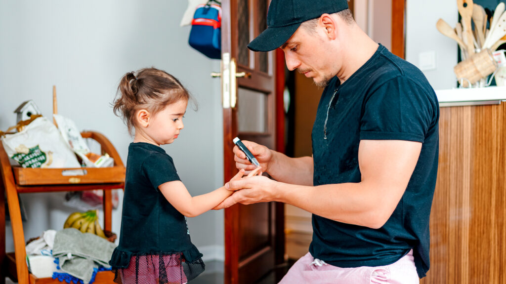 An adult using a glucose monitor to check a child's blood glucose levels