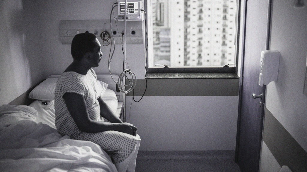 Person sitting on a hospital bed looking out the window