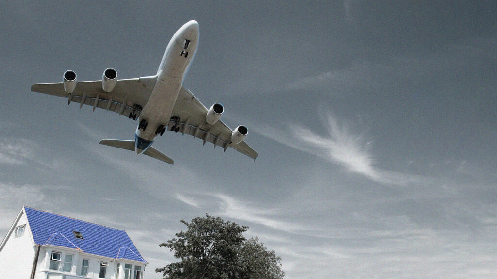 An airplane flying low over a house against a cloudy sky, creating noise pollution.