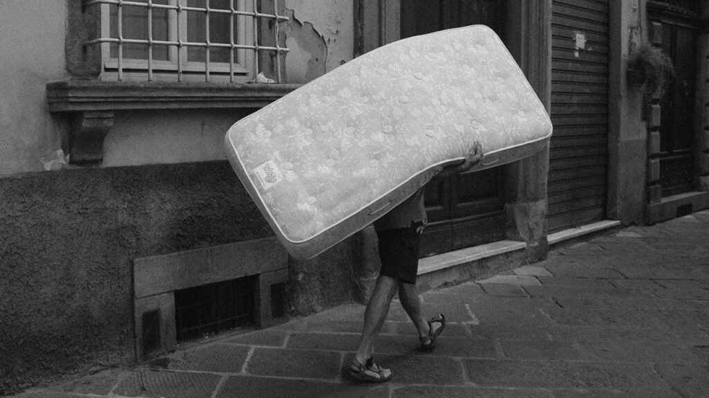 Black and white photo of a person carrying a mattress down a street.