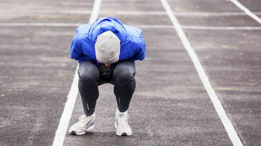 pessoa com uniforme de futebol na pista de corrida curvando-se e sentindo náuseas após o treino