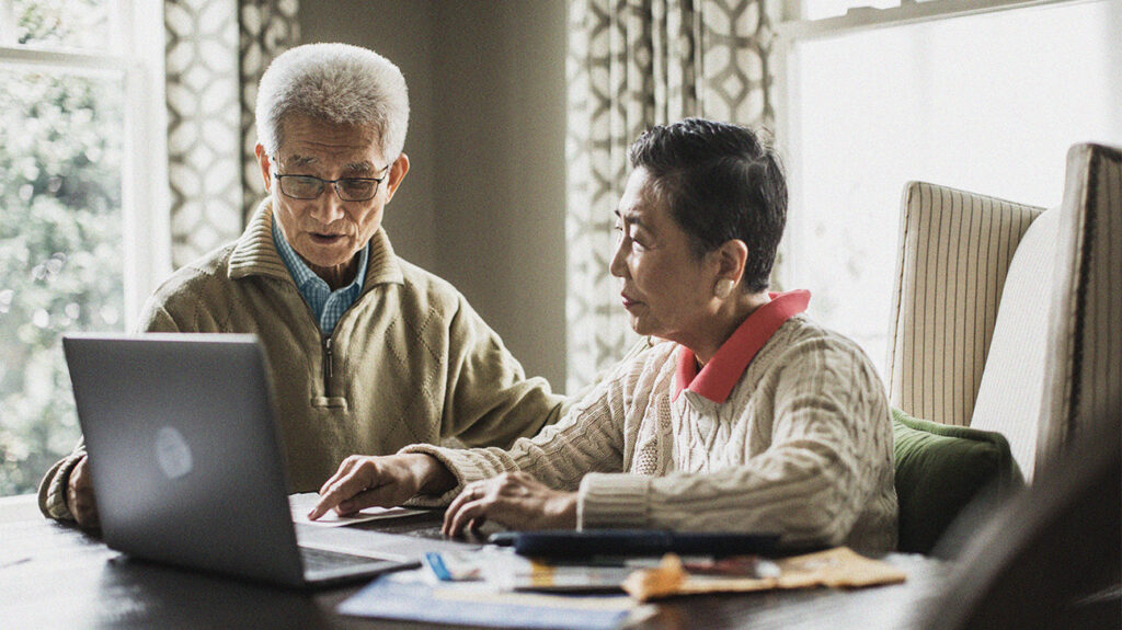Older adult couple using laptop at home that they could use to look for information about the Indian Health Service and Medicare