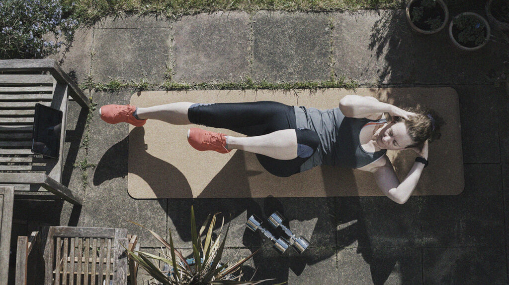 a woman trains to improve muscular endurance by performing sit ups on a yoga mat