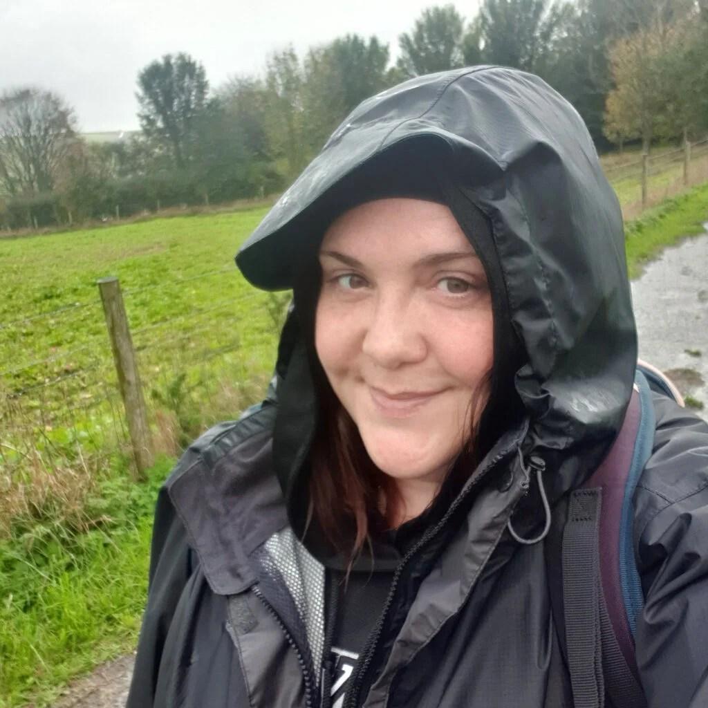 女穿行绿地穿着防水衣行走和在她头上罩,因为它是下雨