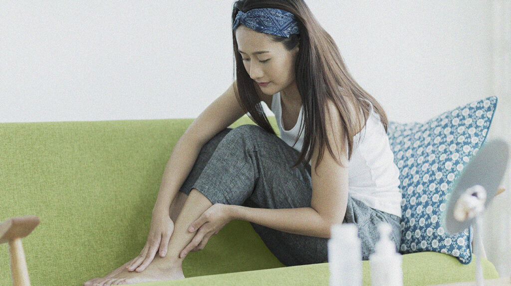 A young woman applying vitamin E for scars to her foot.