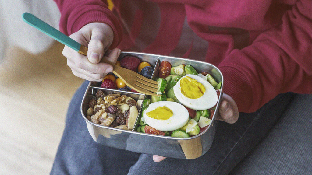 a woman eating a meal out of a lunch box which is part of her warrior diet