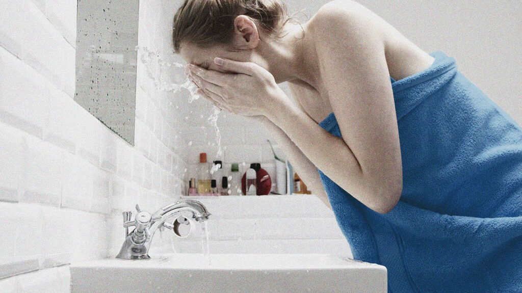 A woman washing her face with water over a sink, in order to treat hormonal acne.