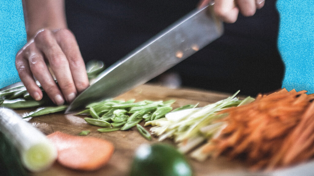 Close up of person chopping ingredients to prepare an organic meal from a delivery kit.