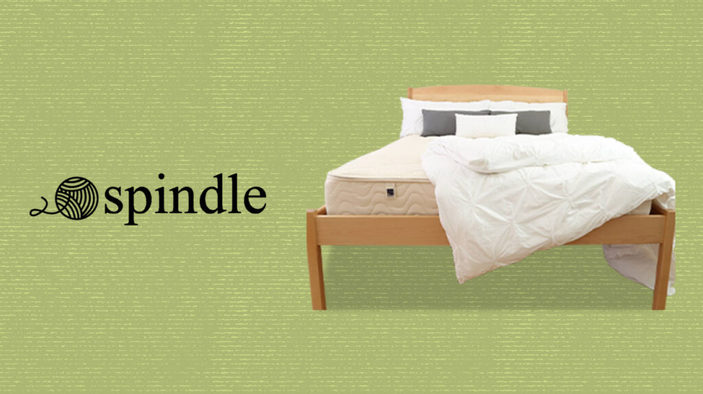 Spindle mattress on a bed frame next to brand logo, over a speckled green background