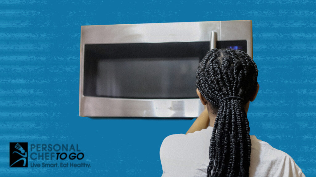 a person waiting at a microwave for their food to cook
