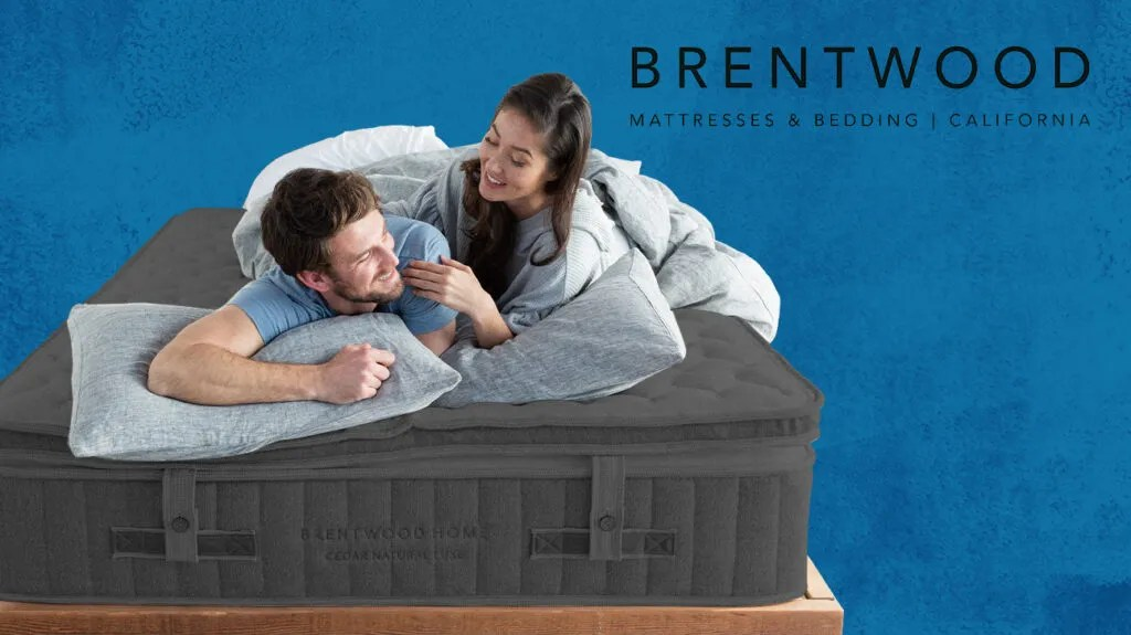 Couple lying on a Brentwood mattress next to brand logo and isolated over a dark blue background