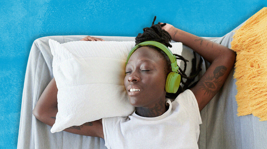 Person sleeping in bed wearing headphones and smiling with their eyes closed