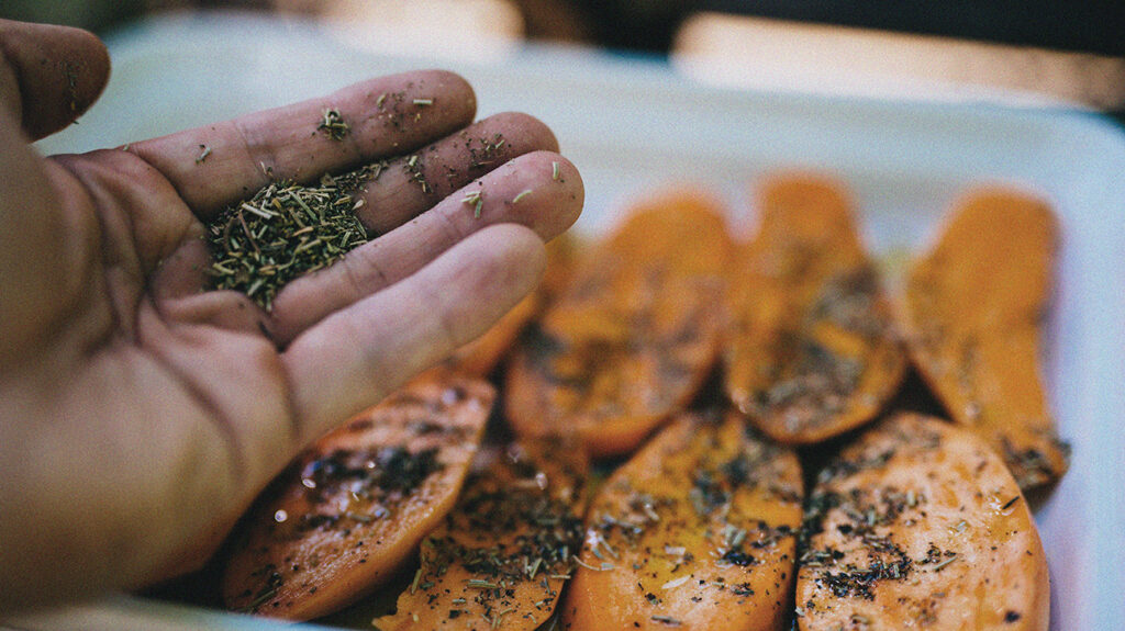 A dish of sliced sweet potatoes, covered with green herbs, ready for the oven.