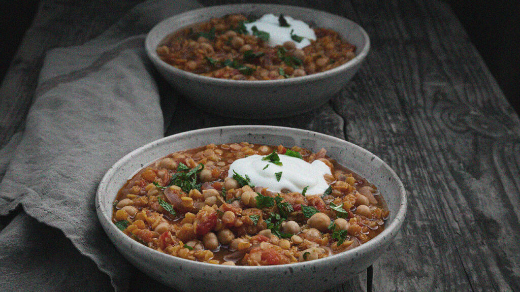 Two bowls of chickpea stew served in tasteful gray bowls. Chickpeas are rich in vitamin B6.