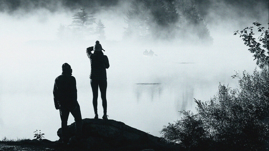 Two people standing on the shore of a lake