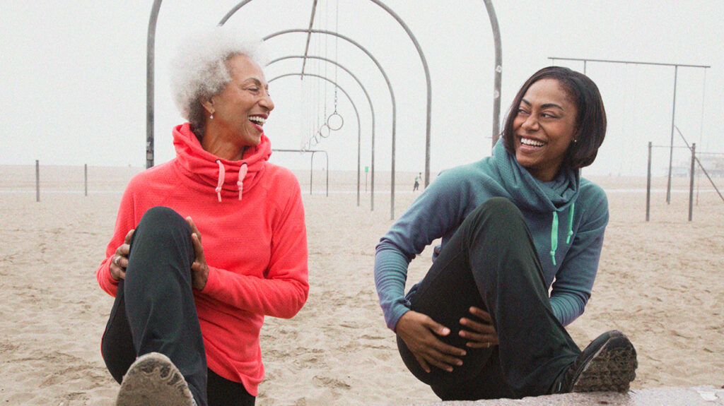 two senior women sitting in the sand laughing wearing jogging clothes
