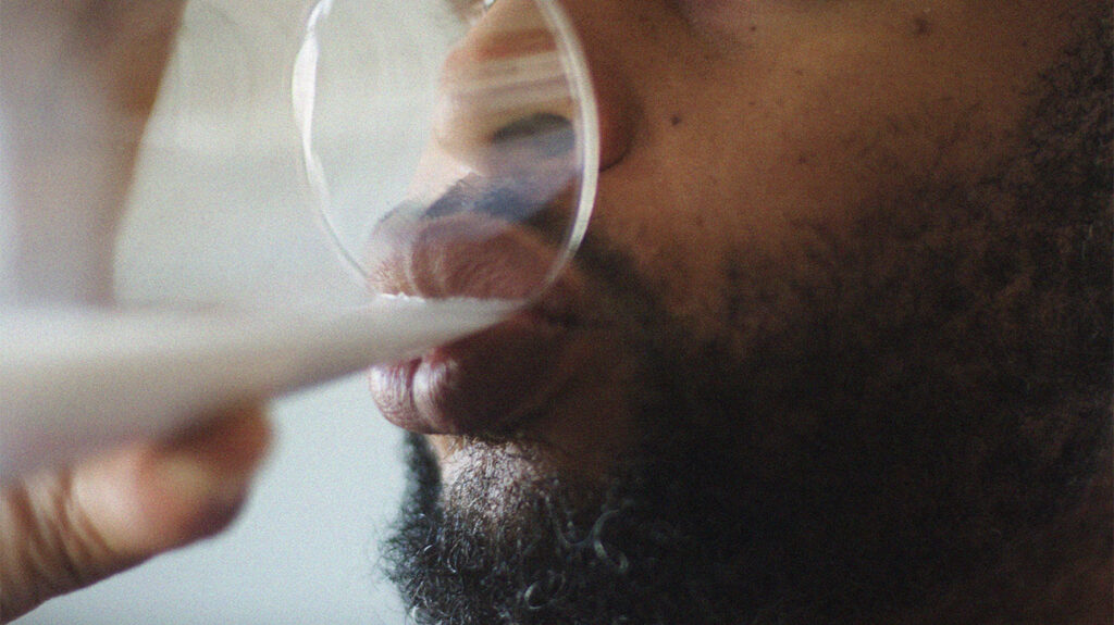 Close up photograph of a man's lips drinking milk from a glass