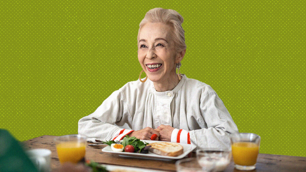 smiling older woman sitting at table in front of meal delivery food for seniors, isolated over green background