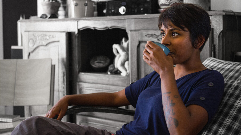 A woman sat in an armchair drinking nettle tea for its potential benefits.