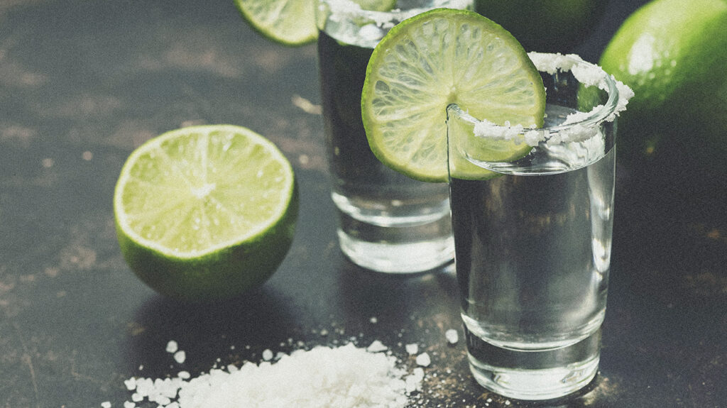 close up of a shot of tequila served with salt and a lime slice, the alleged health benefits of tequila lack scientific support