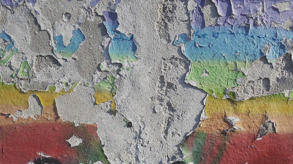 剥掉混凝土墙的彩虹色的油漆。