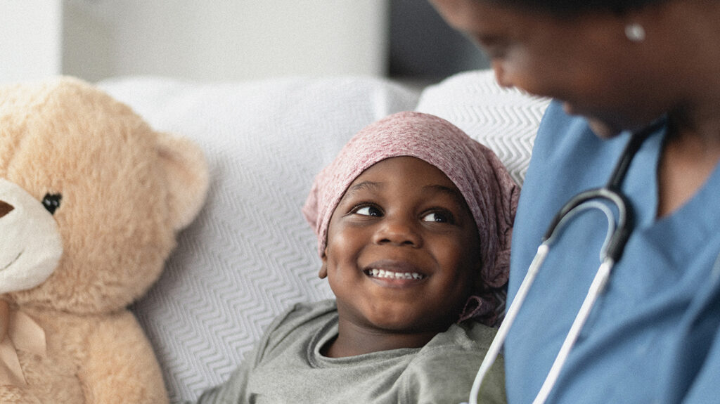 A child wearing a pink head scarf who may have childhood leukemia smiling at someone.