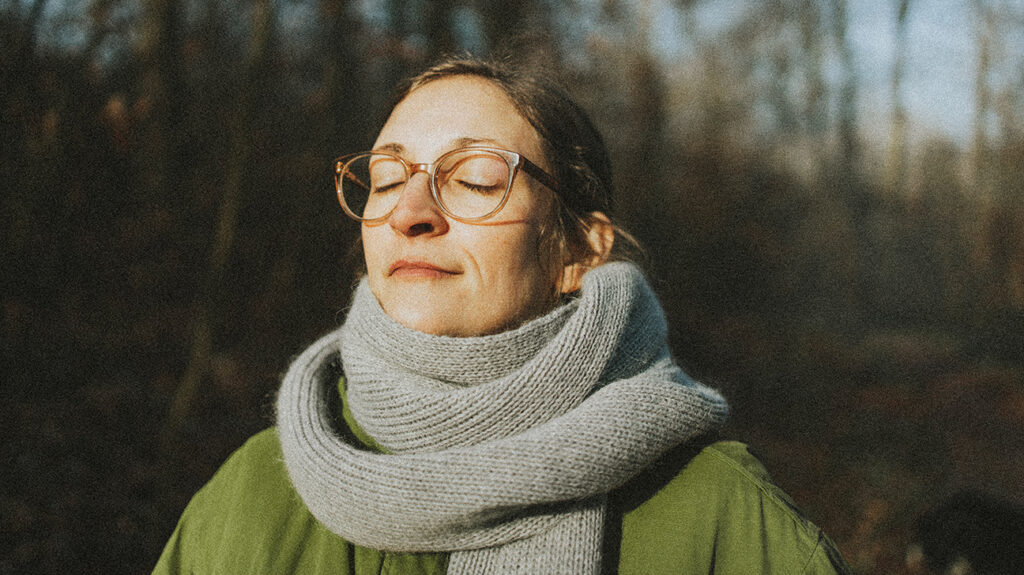 A woman wearing a scarf and glasses, practicing deep breathing as a natural remedy for inflammation.