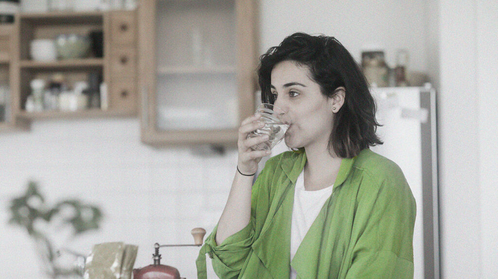 A person wearing a green shirt drinking a glass of water.
