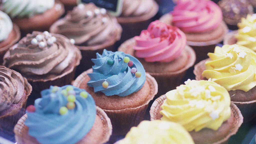 Cupcakes with blue, pink, yellow, or brown frosting that may contain hydrogenated oil.